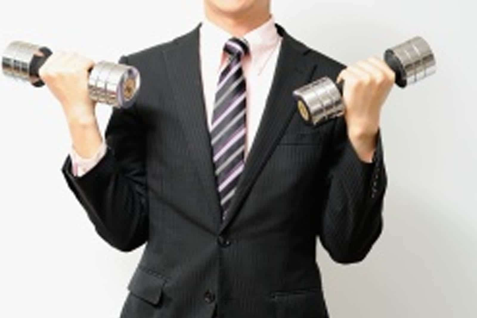 man in a business suit holding weights