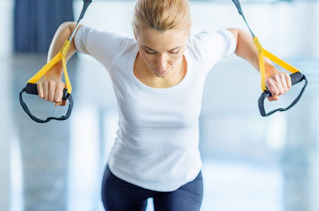 woman with hands in TRX bands doing standing push ups