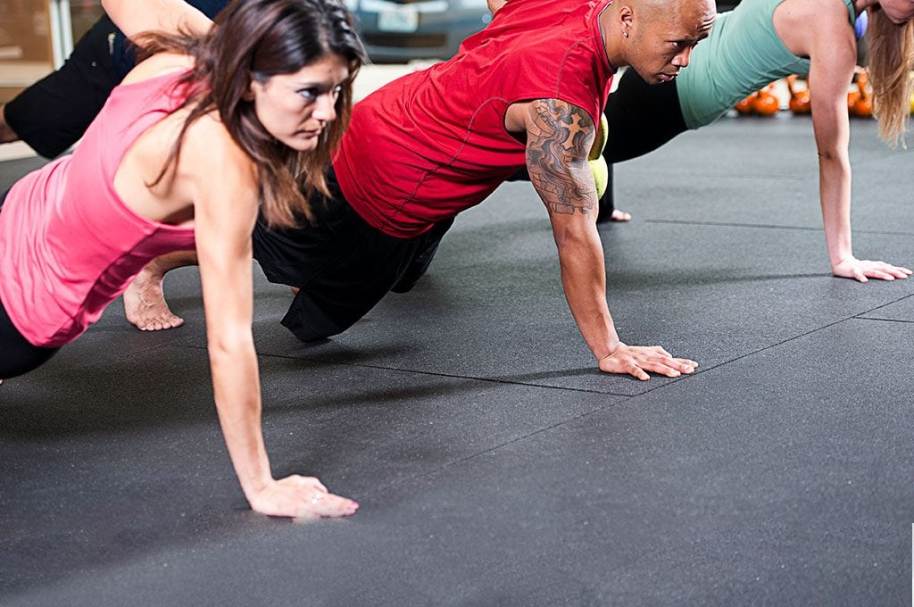 small group of people doing one armed push ups