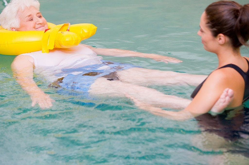 female aquatics therapist working with a woman using a neck float