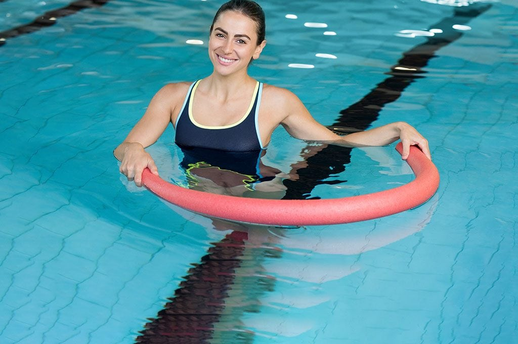 woman in pool holding a pool noodle