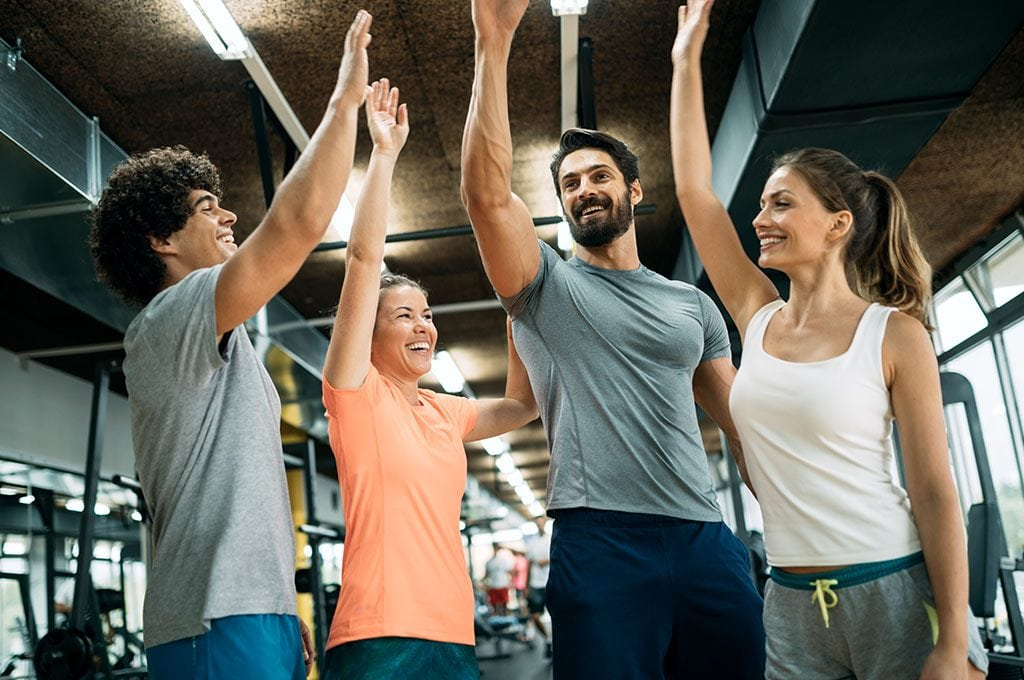 group of fit people high fiving in gym