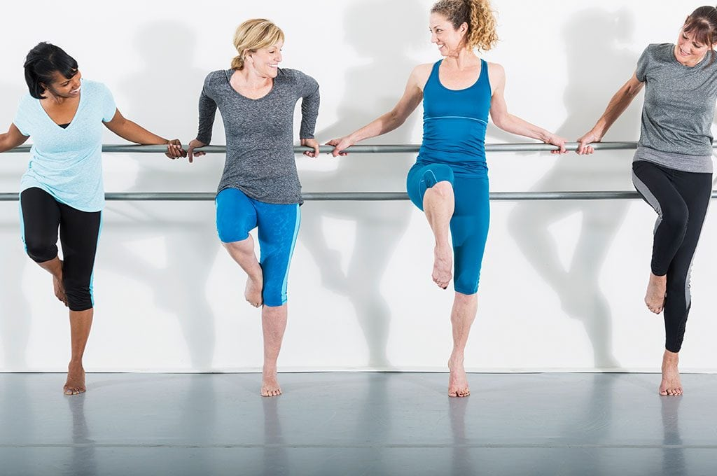 women with thier back to a barre and one leg up with toes pointed