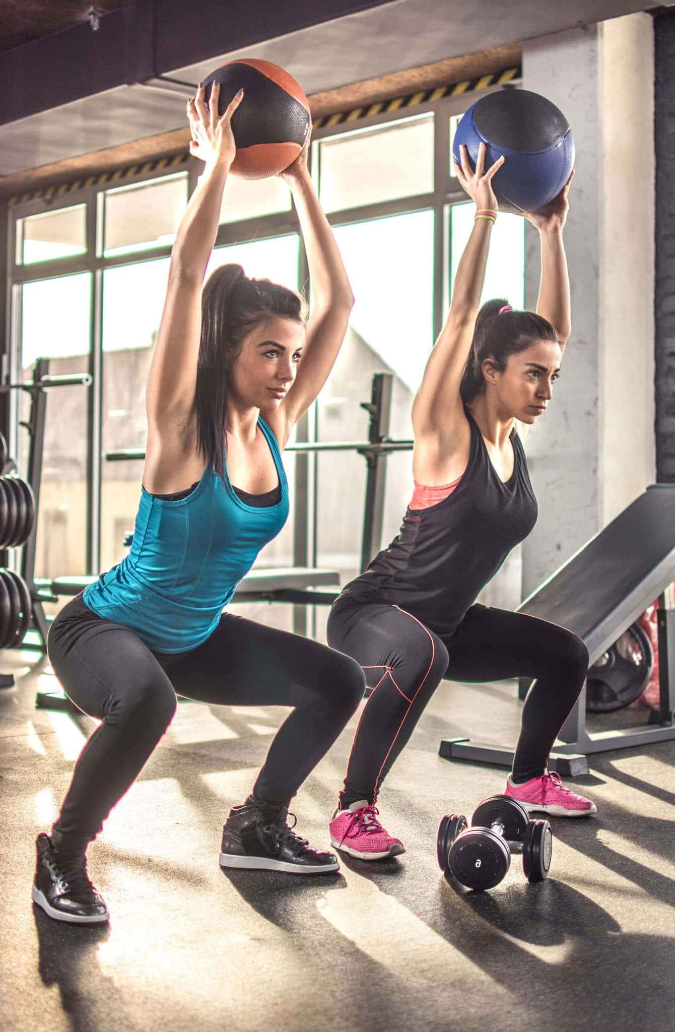 two women lifting kettle bells overhead while squating