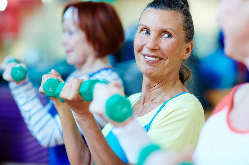 smiling woman lifting 2 pound weights in a fitness group class