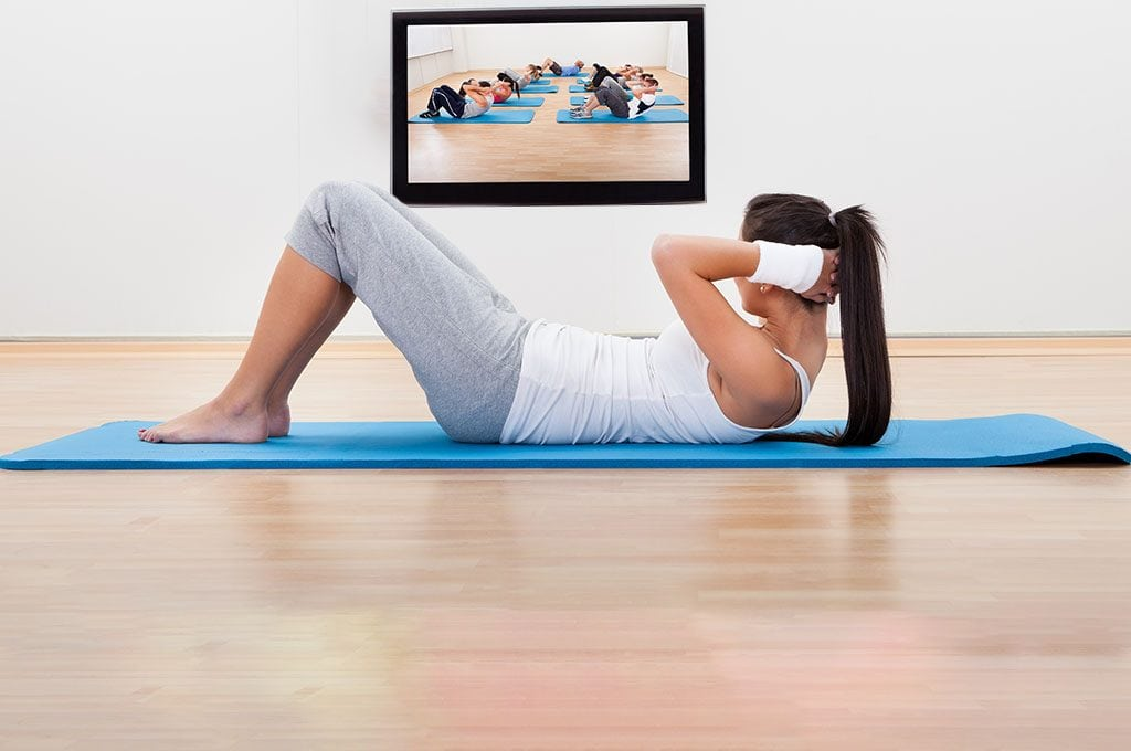 woman doing sit ups while watching a fitness class on TV