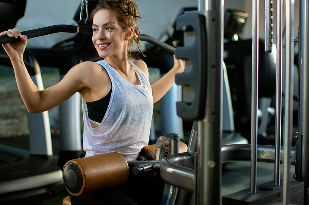 smiling woman on a strength training machine