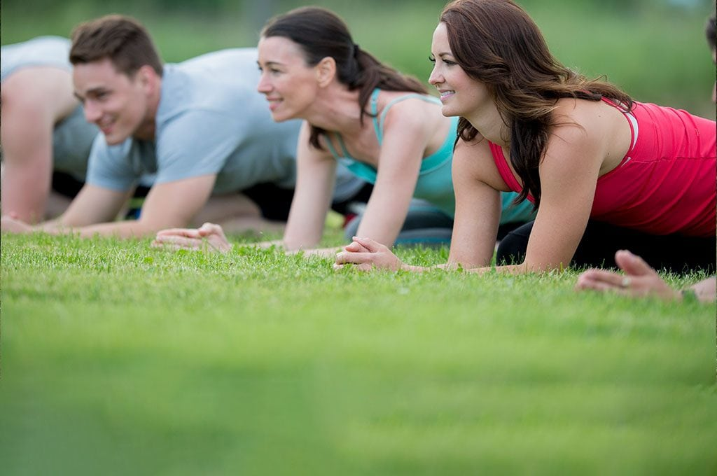 group of smiling people planking on the grass