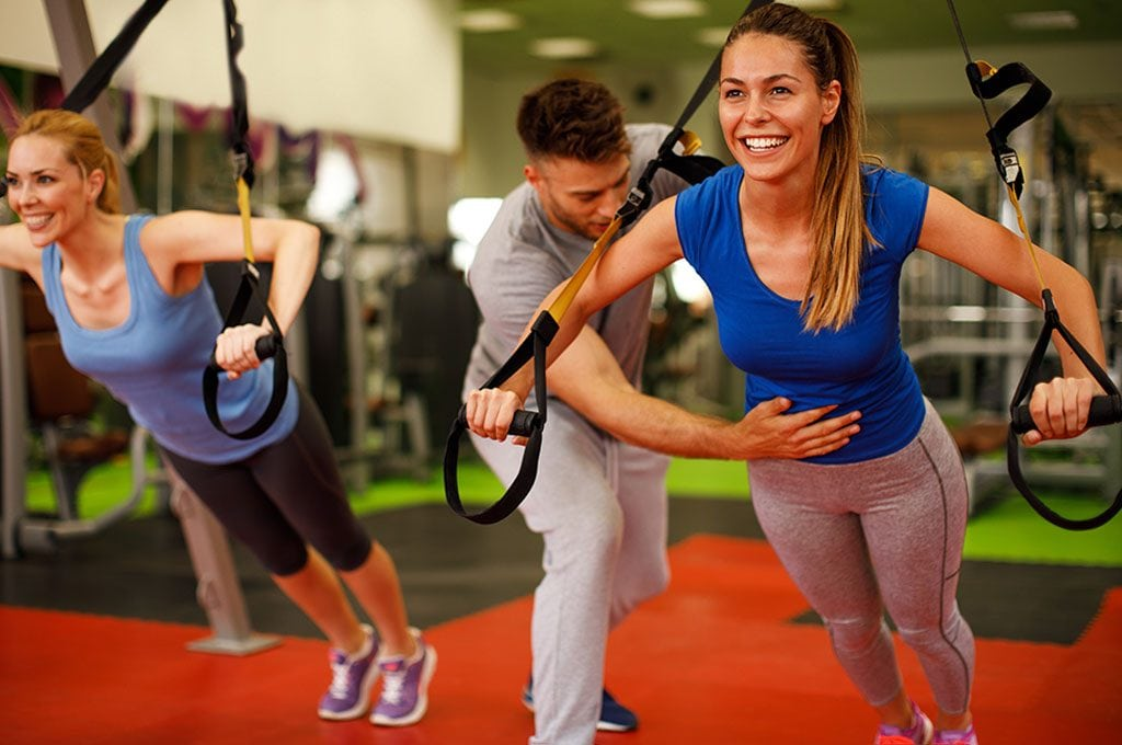 personal trainer shwowing a woman how to properly use the TRX rings