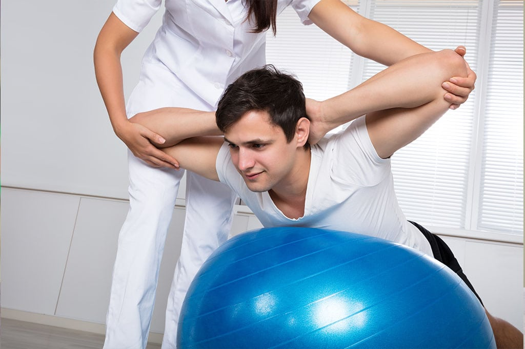 Female physical therapist stretching a man upward on a yoga ball