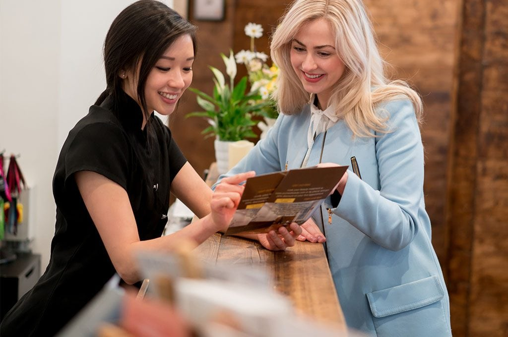 two women at front desk of a salon looking at menu of services