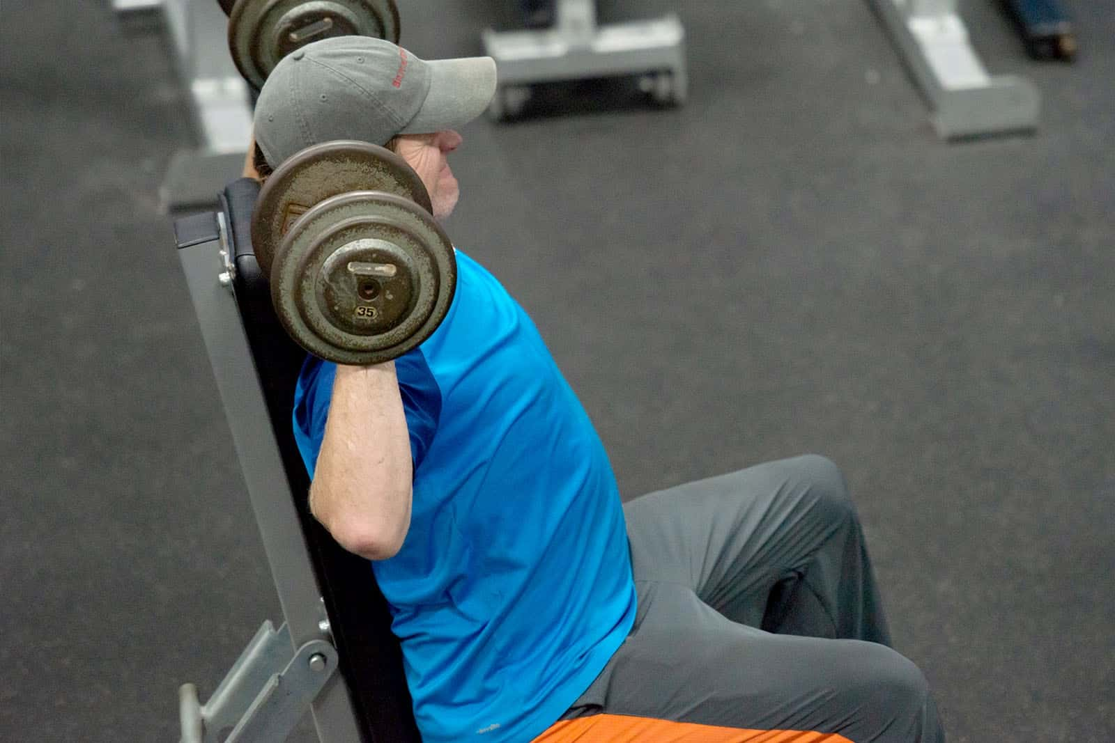 Man in blue shirt lifting weights while sitting