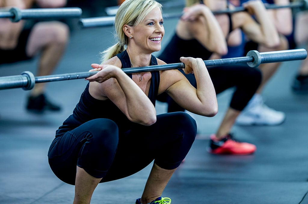 woman lifting a weight bar in a group fitness class