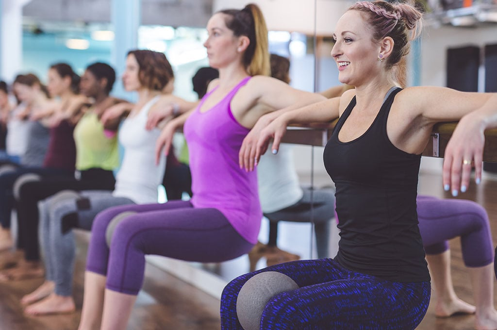 women with elbows on a barre behind them