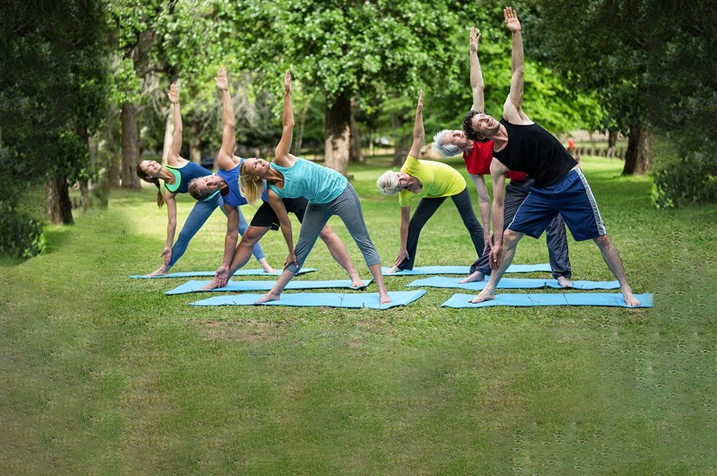 group of people stretching on yoga mats outdoors