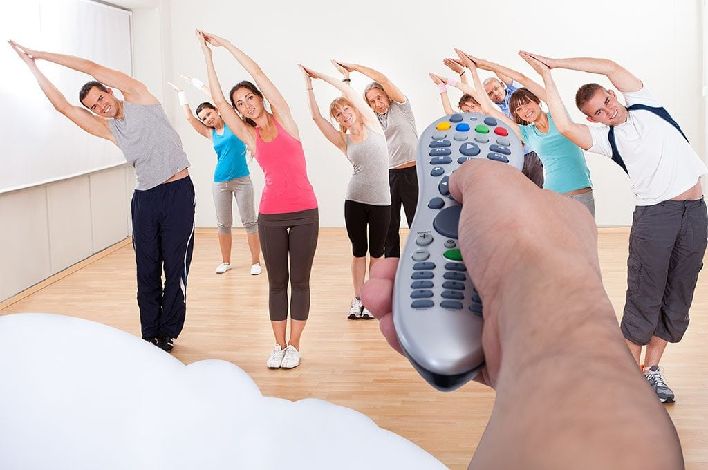 man's hand point remote control to a fitness class on TV