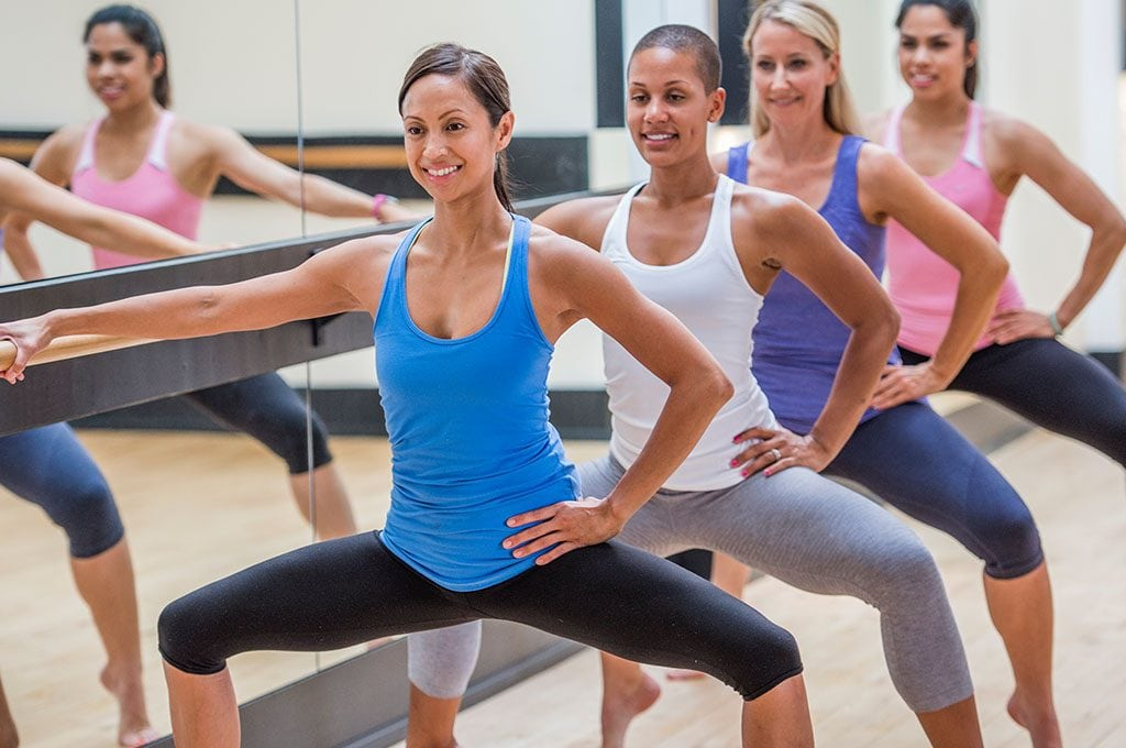 women with one hand on a barre doing a bend at the knees