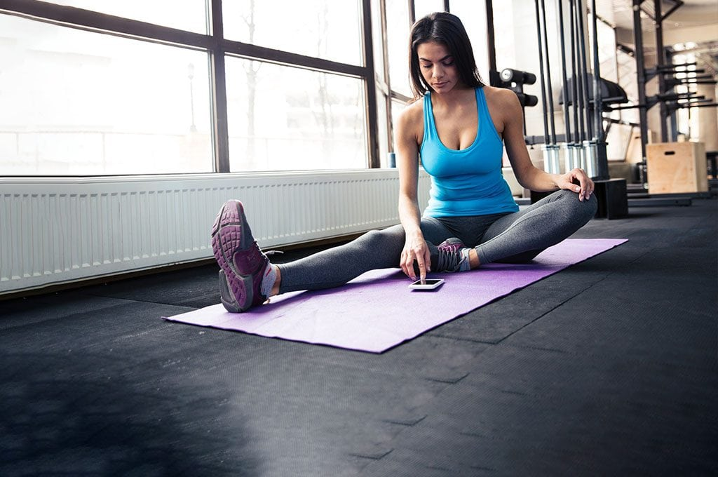 woman sitting on yoga mat checking her BAC app on her phone