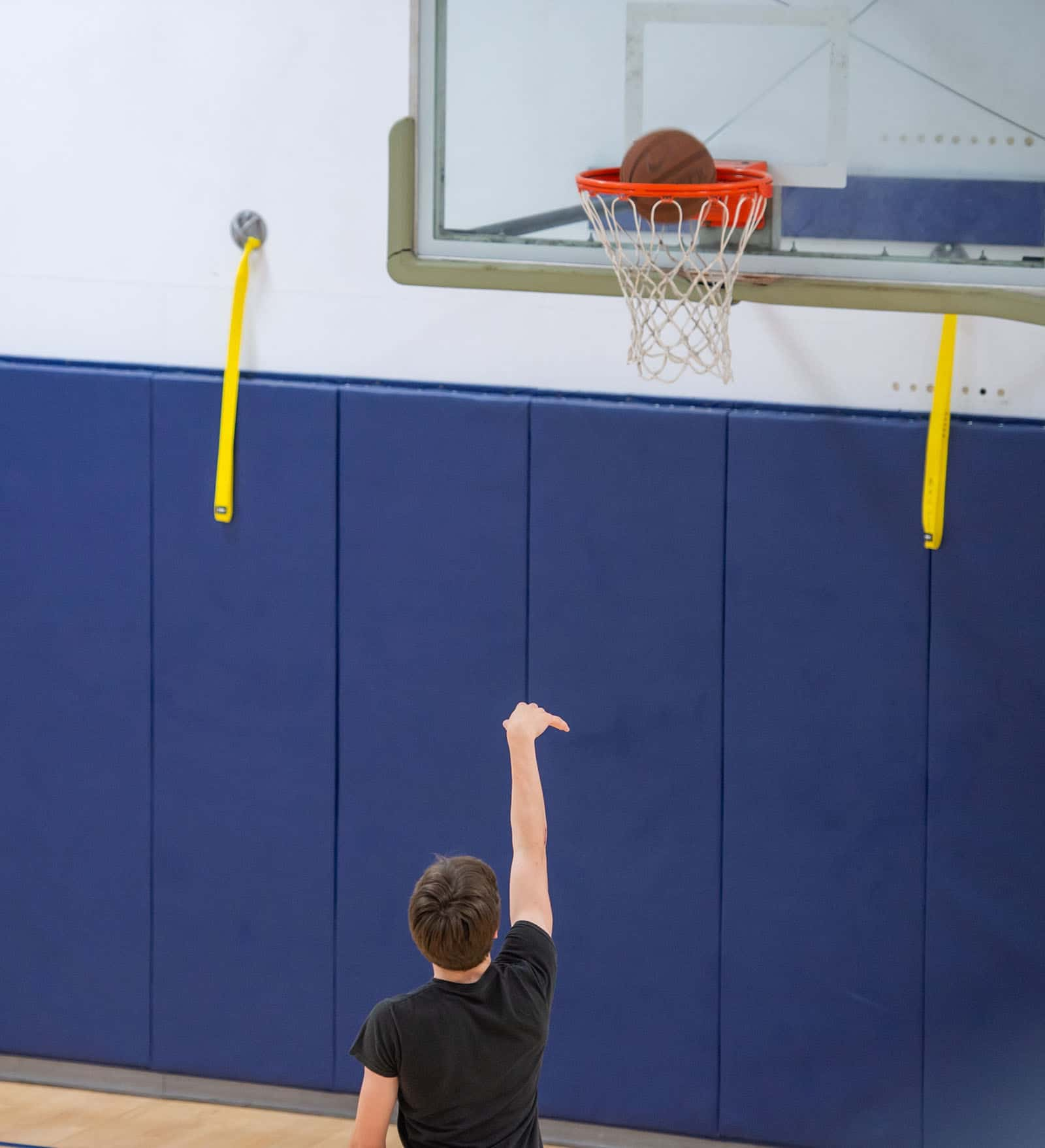 young man throwing a basketball into the hoop