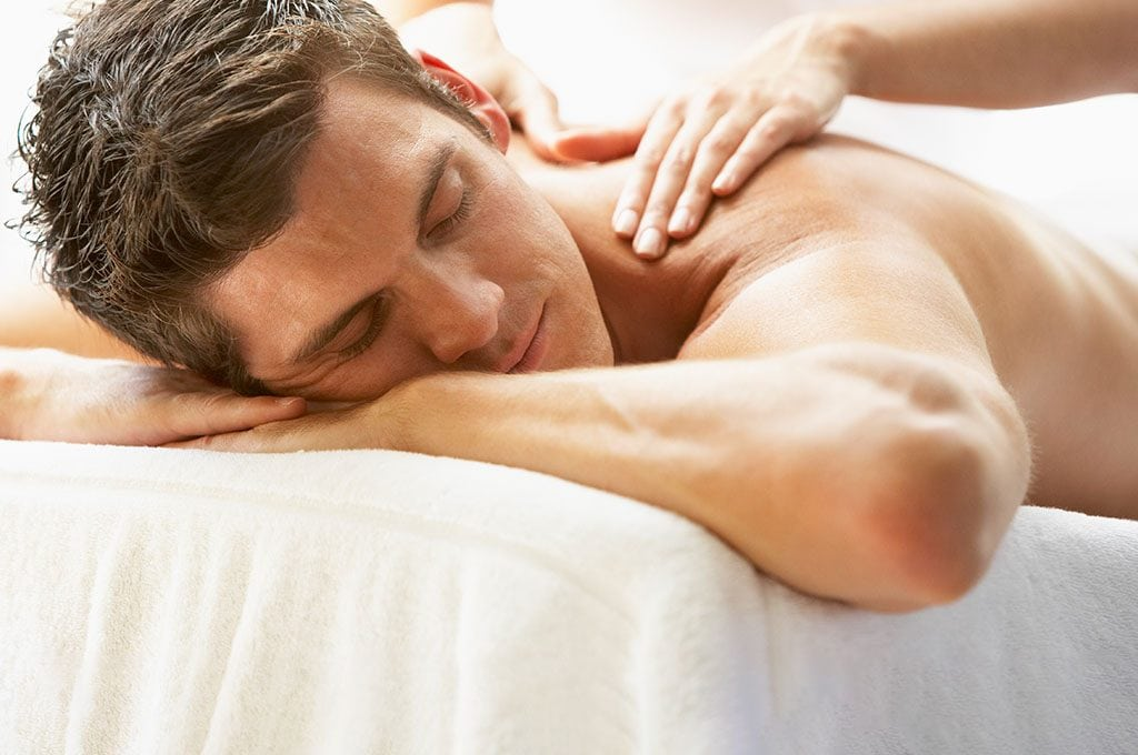 man laying face down on table getting a massage