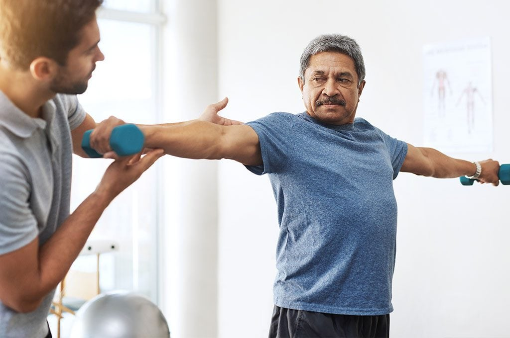 male personal trainer explaining to an older gentleman how to properly use his dumbbells for best results