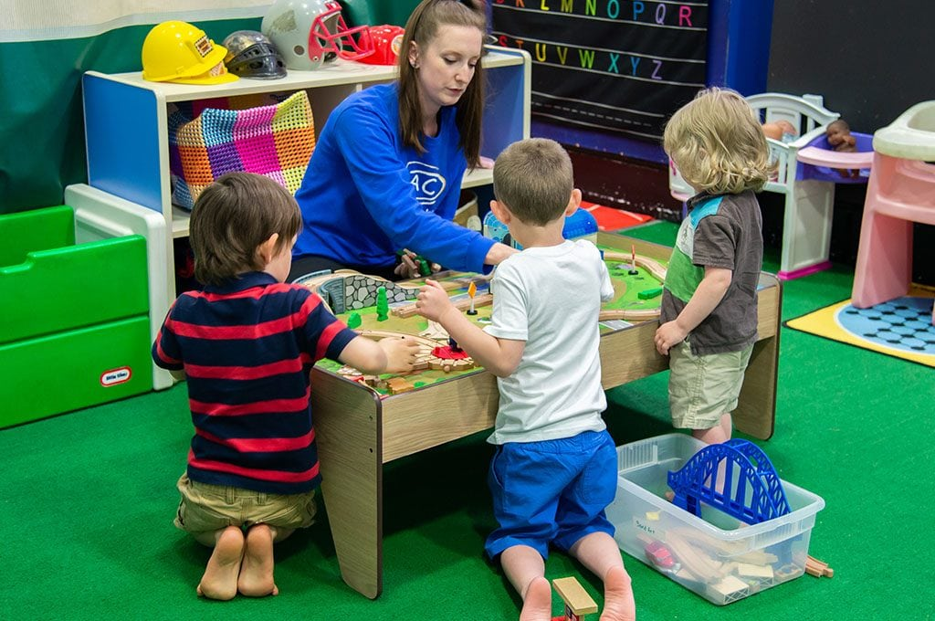 teacher at childcare facility at gym, playing with children