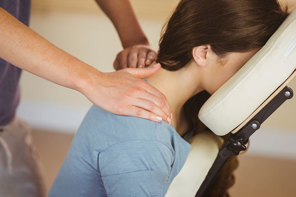 woman sitting face forward in a massage chair