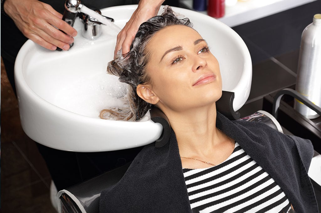 woman getting her hair washed in a salon sink