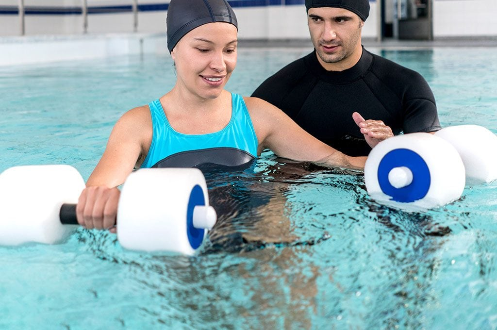 male hysical therapist helping a woman with water weights