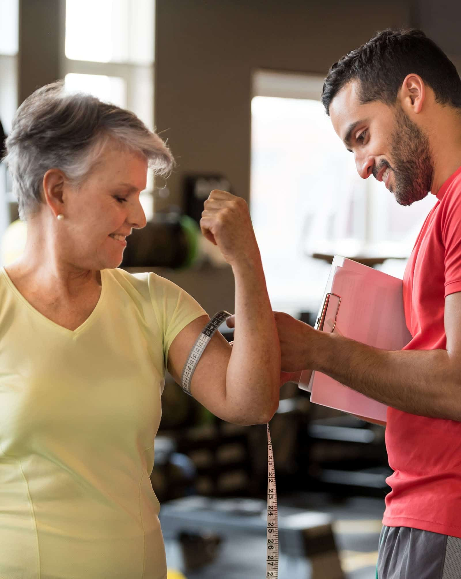 male nutrition and wellness coach measuring a woman's arm