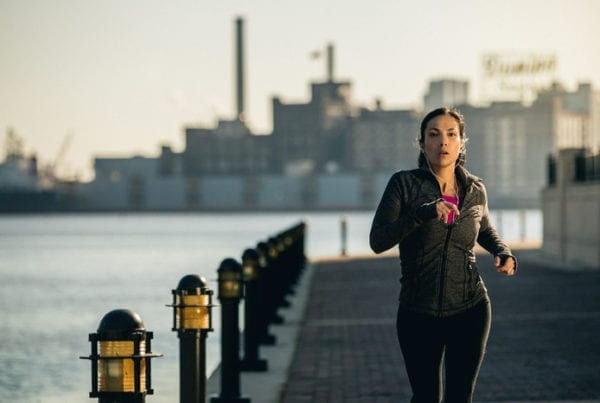 woman jogging in city after receiving fitness tip from brick bodies gyms blog