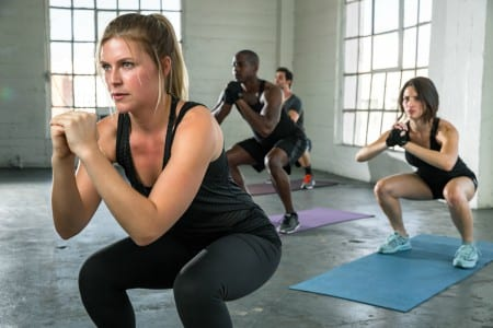 fitness members squatting in strength training group classes at brick bodies reistertown md