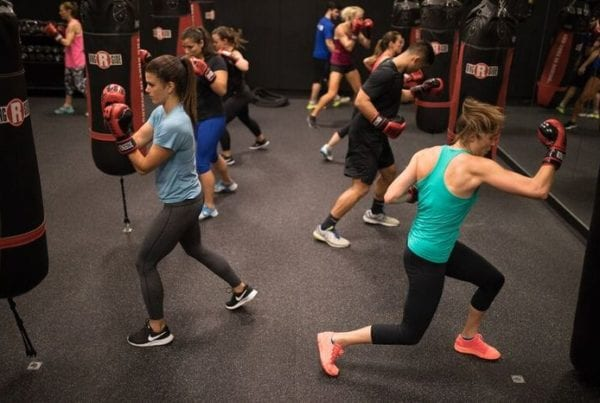 reistertown gym members in group classes wearing gloves and hitting punching bags