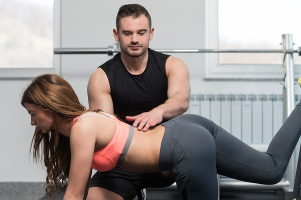 personal trainer at brick bodies padonia assisting gym member with proper body mechanics