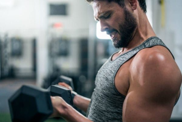 male fitness member using weights and dumbells to improve bicep strength