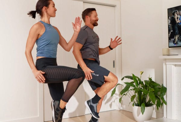 couple at home performing to virtual group fitness classes provided by brick bodies gym