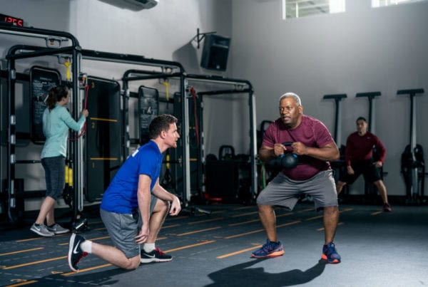 reistertown gym member receiving coaching from personal assistant while squatting with kettlebell