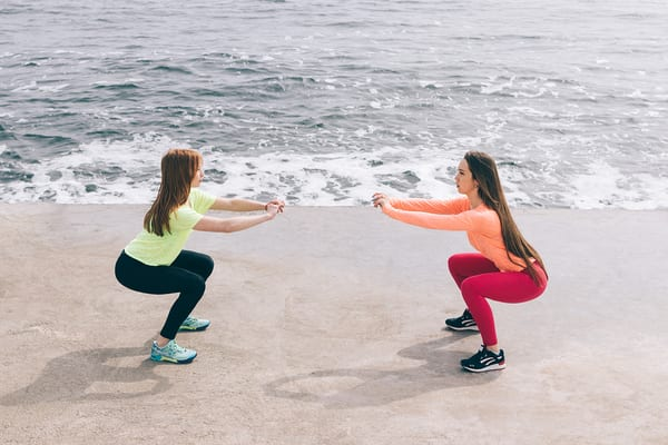 women taking brick bodies gyms tips and squatting while vacationing at beach
