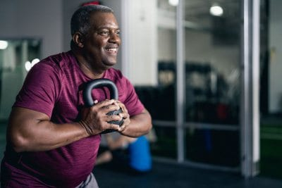 fitness member holding kettlebell while working out in brick bodies gym