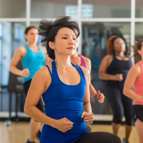 woman in group fitness class using explosive movement at brick bodies padonia