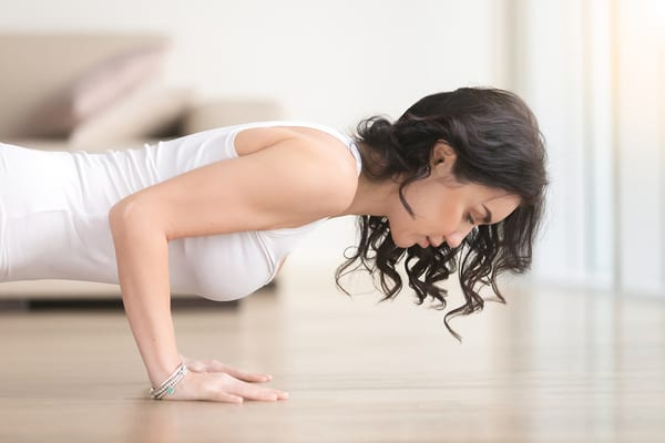 woman in yoga plank position using brick bodies virtual classes in hotel room