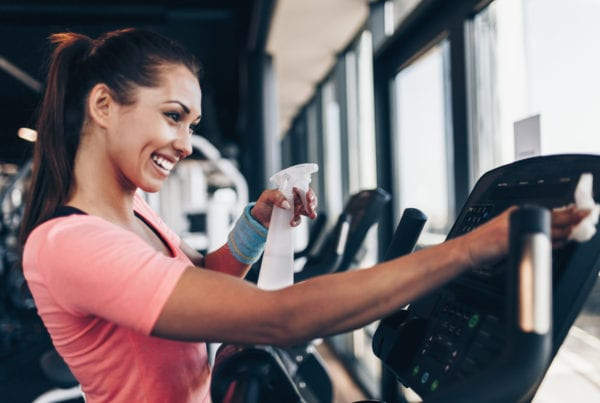 gym member using disinfectant spray and paper towel to wipe down cardio training equipment