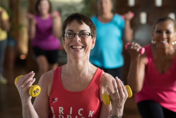 happy brick bodies senior fitness class member using weights to exercise at gym in reistertown
