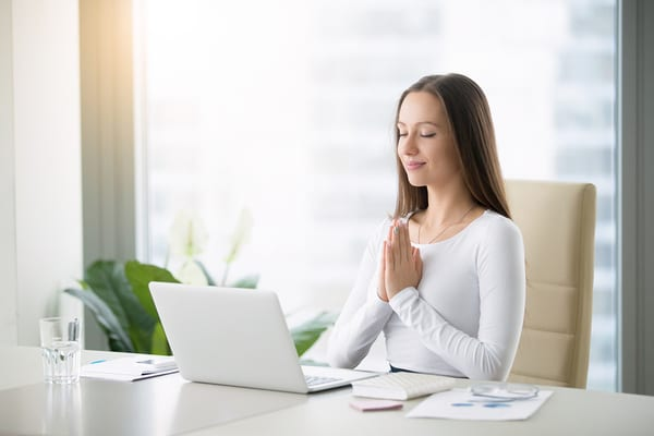 woman at desk watching virtual yoga classes from brick bodies padonia