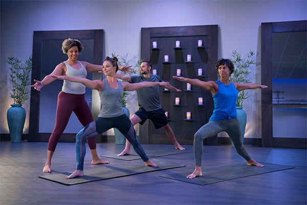 group yoga fitness class in modern gym studio