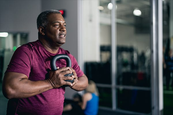 man holding kettlebell close to heart while training at gym near me