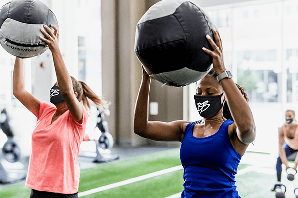 women in bootcamp holding up slam ball with brick bodies masks