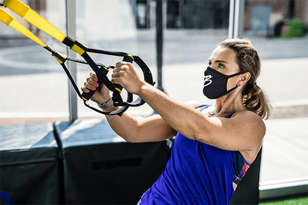 woman using TRX training pulley equipment to strengthen back and arms at gym with brick bodies mask
