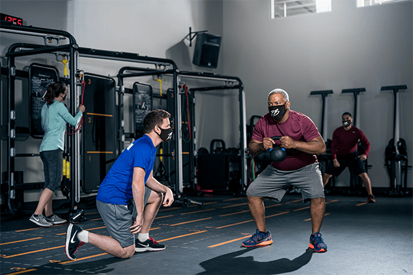 african american male squatting with kettlebell as coach looks on at gym
