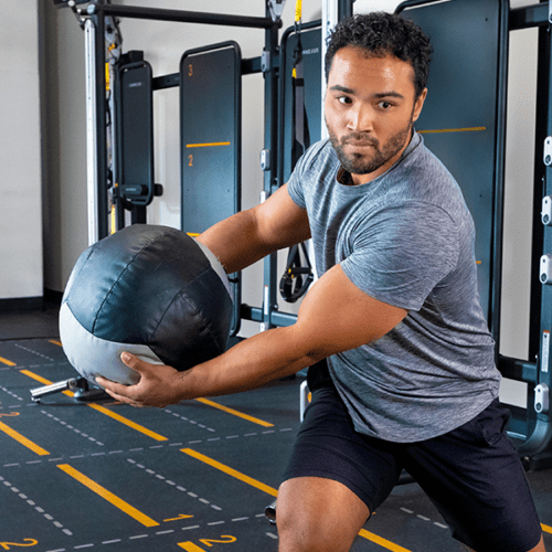 male gym member utilizing the male ball toss in mx4 station
